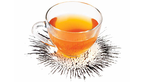 Photo of a cup of orange lique that appears to be sinking into the table.