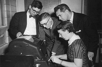 Professor Calvin Gotlieb (with bow tie) and CN Telegraph officials look on as programmer Audrey Bates makes computer history.