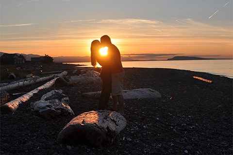 Two figures kiss in front of a sunset.