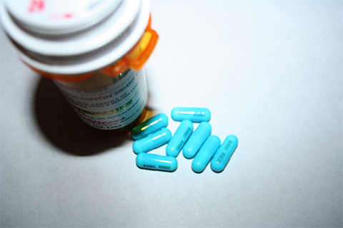 Photo of pills and a bottle.