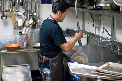 A man working in a kitchen washing dishes.