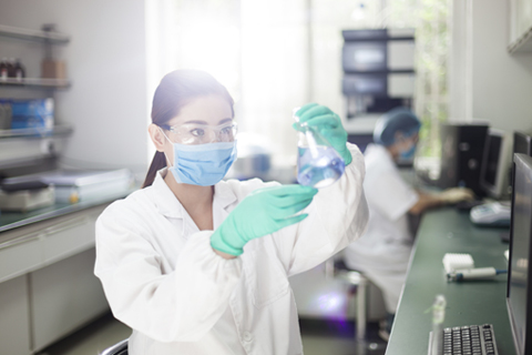 Photo of a doctor or chemist in a lab mixing chemicals.