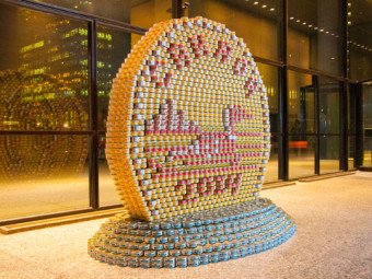 Photo of a giant loonie coin made from tuna cans.