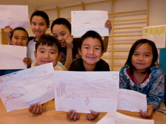 Indigenous children show their illustrations from class.