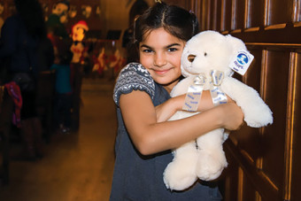 Photo of a young girl with a plush bear.