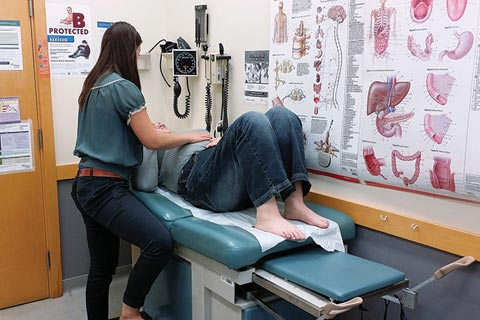 A U of T medical student examines a patient at the IMAGINE clinic.
