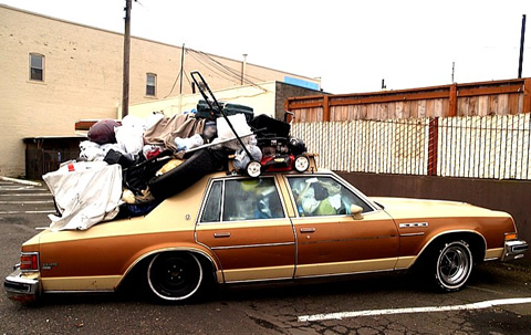 Photo of a pile of stuff on top of a car.