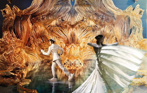 Illustration of two moving figures before an illustrious gold backdrop.