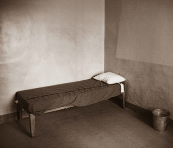 A b&w photo of a single bed in a room.