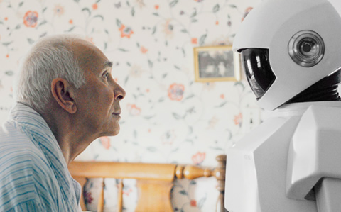 A elderly man and a robot look at one another.