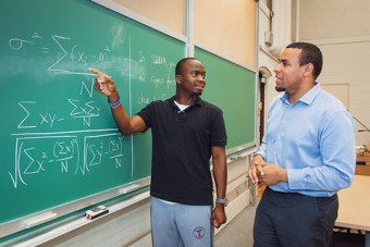 Photo of Akingbade and Okafor at a blackboard in the classroom.