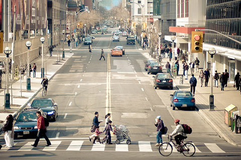 Photo of people crossing a busy city street.