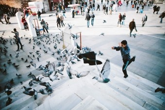Boy launches jacket on the steps of Yeni Cami and pigeons fly