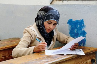 Photo of a young woman writing a test in school