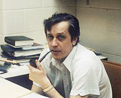 Photo of Adam Becker at his desk smoking a pipe
