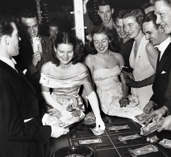 Black and white photo of students in gowns and tuxedos placing bets around a roulette table