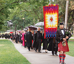 Photo of the convocation procession from Victoria College with bagpiper Rory Sinclair at the lead