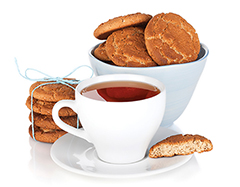 Photo of a cup of tea and cookies in a bowl, on the side and one half eaten