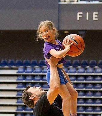 Photo of a man lifting up a smiling girl holding a basketball at the Golding Centre