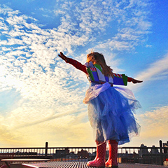 Photo of a girl in a dress and boots with her arms stretched wide
