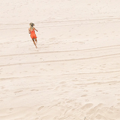 Photo of a girl in an orange bathing suit, running on a beach