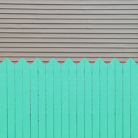 Photo of light grey horizontal lines in the upper half and light green, vertically lined picket fence in the bottom half