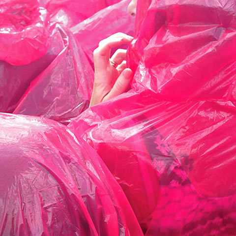 Photo of a hand poking out from under a pile of red-pink plastic bags
