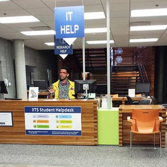 Photo of Drake behind the IITS Student Helpdesk, wearing red glasses
