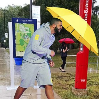 Photo of Drake walking on UTSC grounds, holding a yellow umbrella