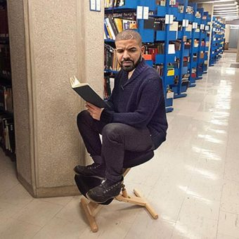 Photo of Drake reading a book among the UTSC library stacks
