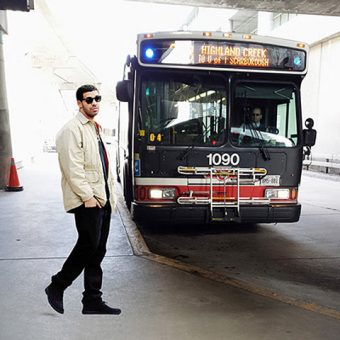 Photo of Drake waiting for an approaching bus at UTSC