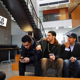 Photo of Drake sitting on a bench at UTSC with two friends