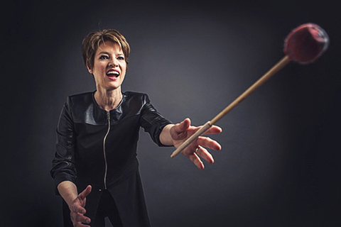 Photo of Beverley Johnston with hands out and a mallet in the air