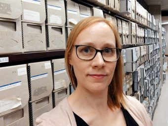 Photo of Karen Suurtamm in front of shelves of archived records