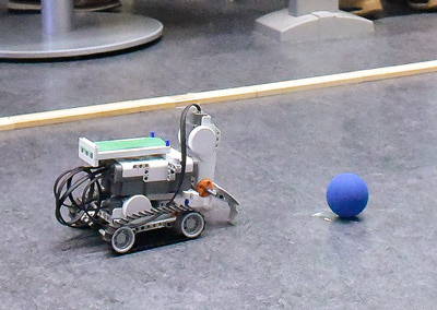 Photo of a small robot with wheels in front of a ball