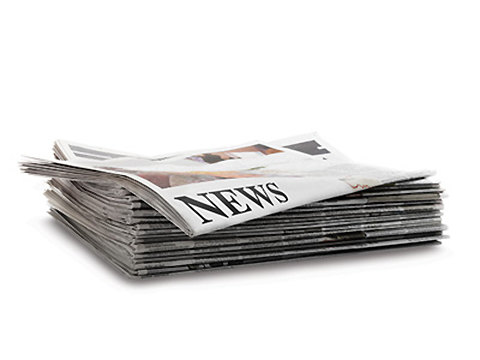 Photo of a stack of newspapers with the headline