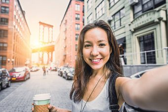 Selfie photo of a woman holding a coffee cup in the middle of a street
