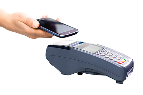 Photo of a hand holding a cell phone over a portable card machine