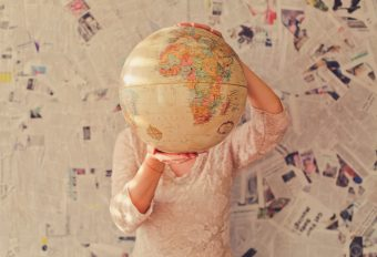 Photo of a person holding a globe in front of themselves.