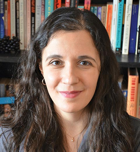 Headshot of Rebecca Rosenblum in front of a bookshelf