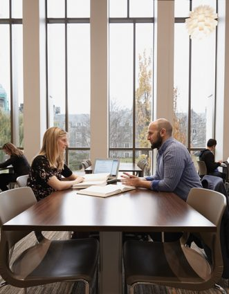 """Students Stephanie Lewis and Zachary al-Khatib work together at the Bora Laskin Law Library in the new Jackman Law Building. """"Collaboration is essential to every part of the law school process,"""" says al-Khatib. Photo by Caroline Ryan."""