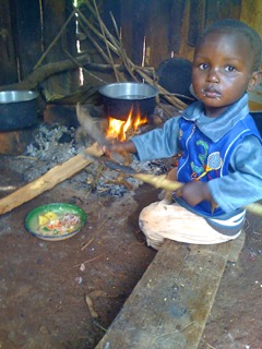 Photo of a child playing in front of a cooking fire