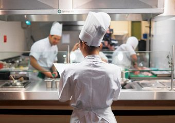 Backup member Ailin Xi overlooking U of T's Iron Chef team while they are working in the kitchen