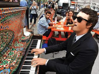 Photo of Sebastian Brown with sunglasses and a cigar in mouth, playing piano on the street, and onlookers at a picnic bench