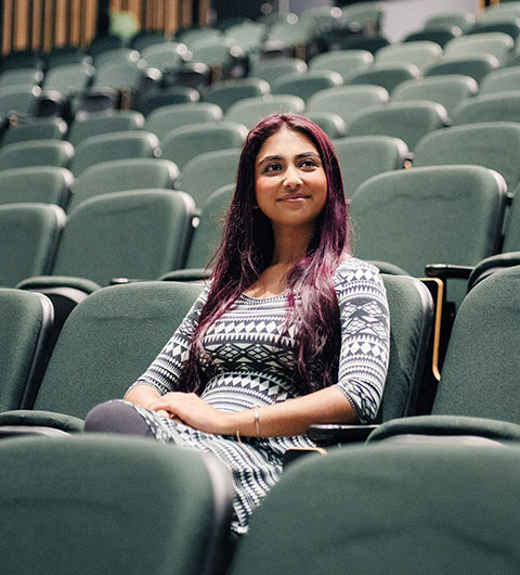 Muhaddisah Batool sitting in a seat in an empty theatre
