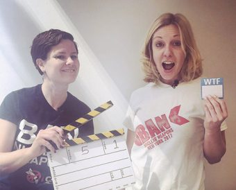 "Ray Acheson holding a movie clapboard and Allison Pytlak holding a tag with the letters ""WTF."""