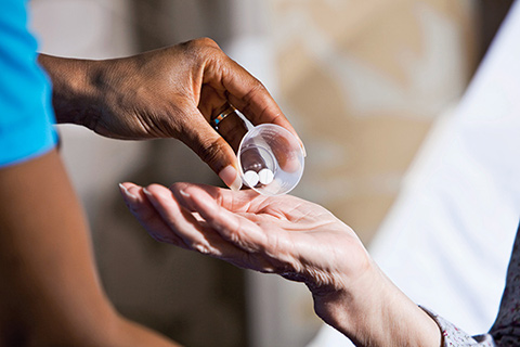 Close up shot of a medical provider's hand tipping two pills onto a patient's hand