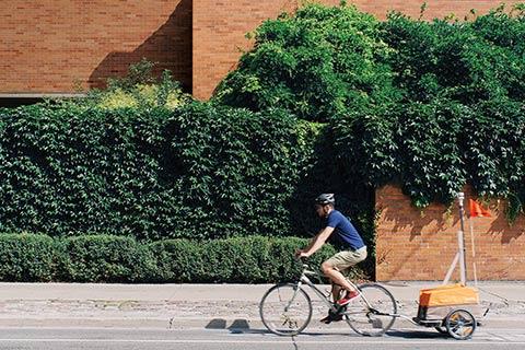 Photo of Colin Arrowsmith biking along Huron Street, pulling a device.