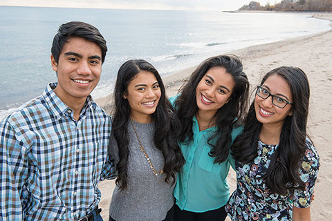 Photo of the Syed siblings standing on a beach, smiling at the camera.