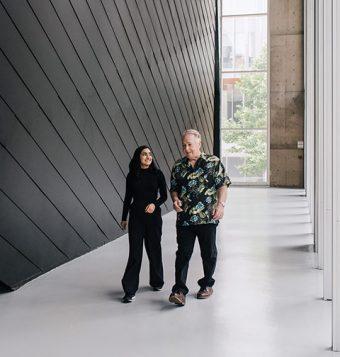 Photo of Ishveer Malhi and Ken Luckhurst walking and conversing inside a UTM building.